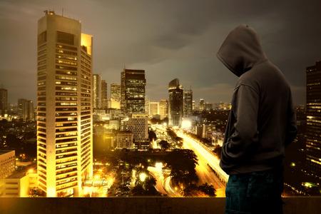밤에 건물의 상단에 서있는 두건을 된 남자의 컴퓨터 해커 실루엣
