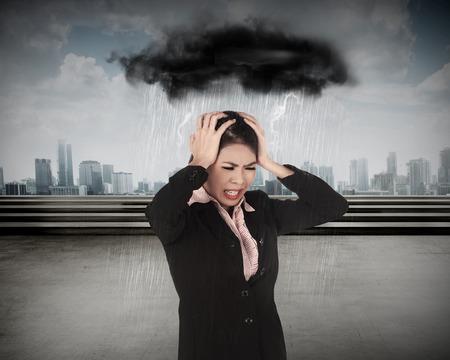 sotto la pioggia: Giovane donna asiatica di affari sotto la testa di copertura pioggia con le mani