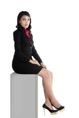 Asian business woman sitting on the block isolated over white background Stock Photo