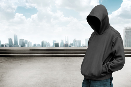 faceless: Faceless man in hood with cityscape background