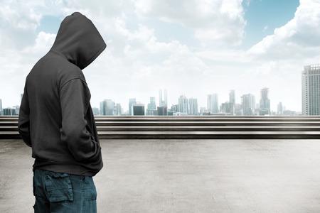 都市景観の背景を持つフード フェースレス男 写真素材