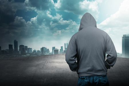 hooded top: Faceless man in hood on the rooftop with city background