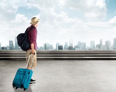 maleta: Joven que viaja a pie asi�tico en la ciudad llevar una maleta