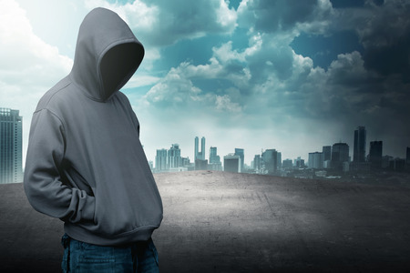 faceless: Faceless man in hood on the rooftop with city background