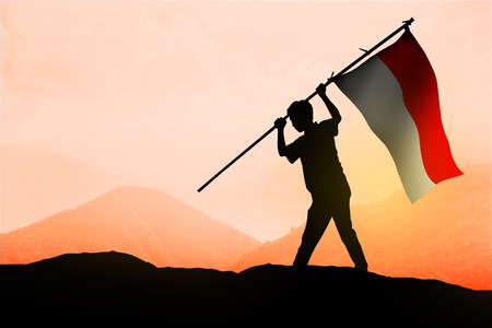 Successful silhouette man waving Indonesian flag on top of the mountain peak