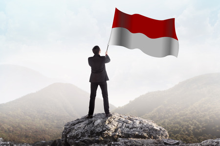 Successful man waving Indonesian flag on top of the mountain peak