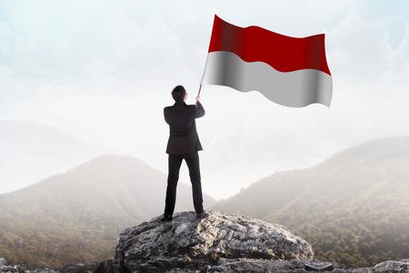 Succesvolle man zwaaien Indonesische vlag op de top van de berg