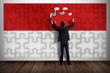 Business man assemble indonesian flag from jigsaw. Independence day concept Stock Photo