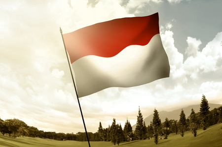 Indonesian flag waving on the hill with blue sky background Stock Photo