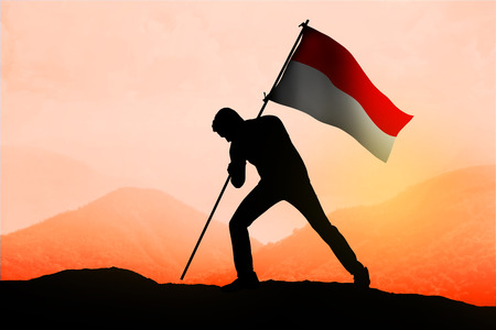 indonesia: Successful silhouette man waving Indonesian flag on top of the mountain peak
