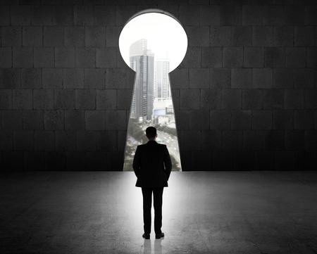 open door: Concept of success business man looking through key hole Stock Photo