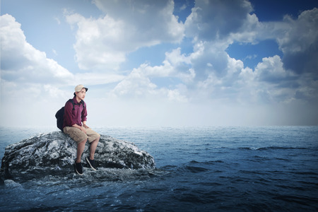 business traveller: Young asian traveler sitting on the rock in the middle of the sea