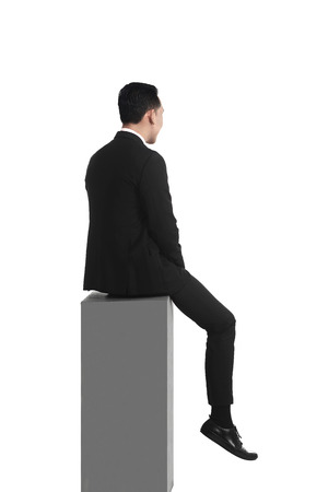 in behind: Backview asian business man feeling sad sitting on the box isolated over white