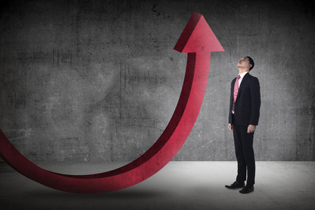 Business man standing looking red arrow up. Business forecasting concept