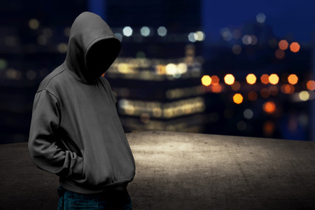criminals: Faceless man in hood on the rooftop with city background at night time