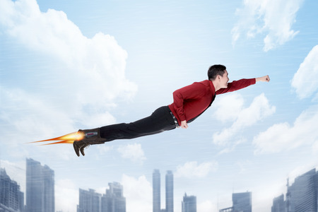 flying man: Business man flying with rocket on his shoes.Job promotion concept