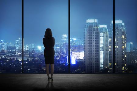 여자는 밤에 도시를 찾고 자신의 사무실에서 서. 비즈니스 성공의 개념