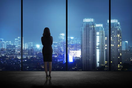 gente exitosa: Mujer de pie en su oficina mirando a la ciudad por la noche. El �xito del negocio concepto