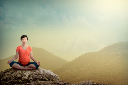 pregnant exercise: Pregnant woman doing yoga on the top of the mountain