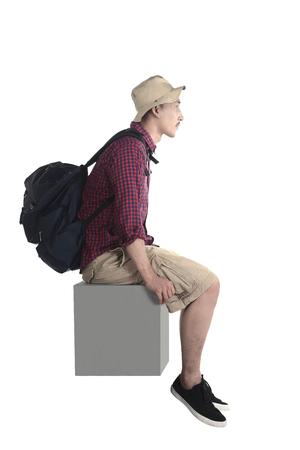 Turista joven sentarse en el bloque aislado sobre fondo blanco