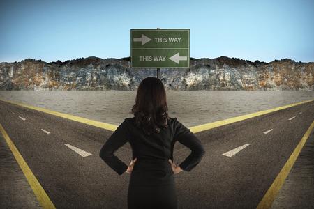 simbolo uomo donna: Donna asiatica in piedi nel mezzo della strada trasversale pensare direzione