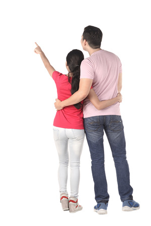 pointing finger up: Young asian couple pointing something isolated over white background