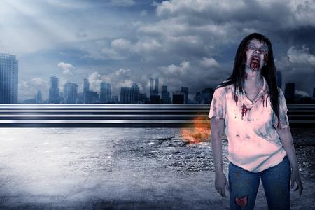 Creepy female zombie walking on destroyed city background