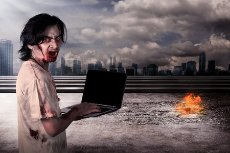 Creepy male zombie typing with laptop with city on fire background