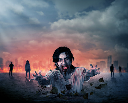 Creepy male zombie out from the ground with destroyed city background