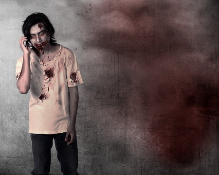 cell: Creepy male zombie talking via cellphone over grunge background Stock Photo