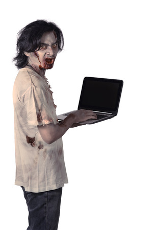 bloodthirsty: Creepy asian male zombie typing with laptop isolated over white background Stock Photo