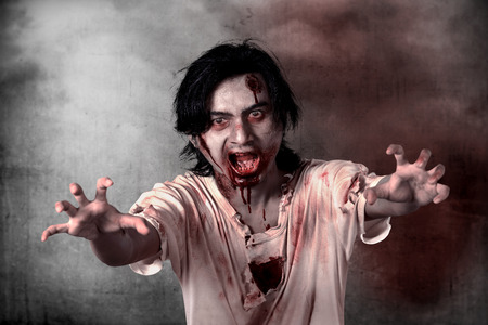 face zombie: Creepy male zombie standing over grunge background Stock Photo