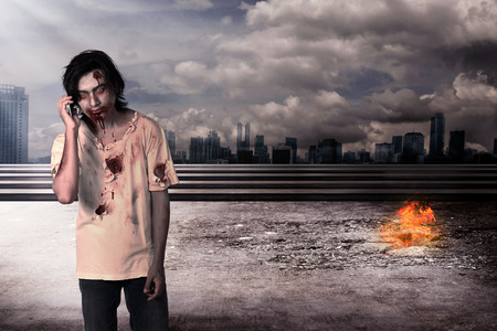 zombie: Male zombie call via cellphone with city on fire background Stock Photo
