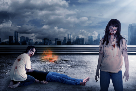 indonesian woman: Group of zombie eating flesh with destroyed city background