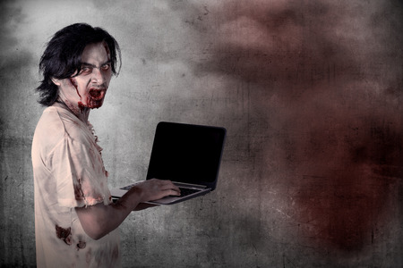 zombie: Scary male zombie typing with laptop over grunge background Stock Photo