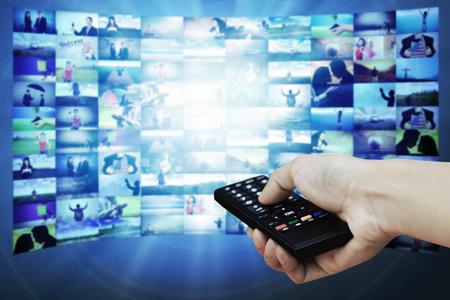 viendo television: Big panel de TV con imágenes de transmisión en la televisión y el control remoto en la mano