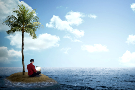 alone person: Business man working with laptop on the small island on the sea Stock Photo