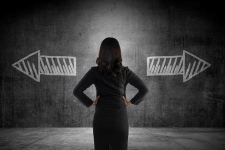 liderazgo empresarial: Mujer de negocios que tiene que elegir entre dos vías. Opción conceptual de negocios