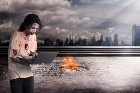 nuke: Creepy male zombie typing with laptop with city on fire background