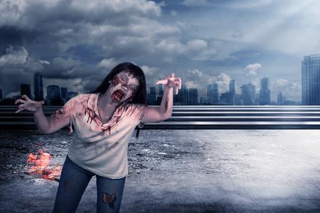massacre: Scary female zombie with burning city background. Halloween concept