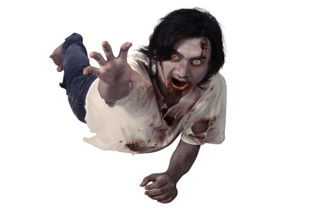 Male zombie crouching on the floor isolated over white background