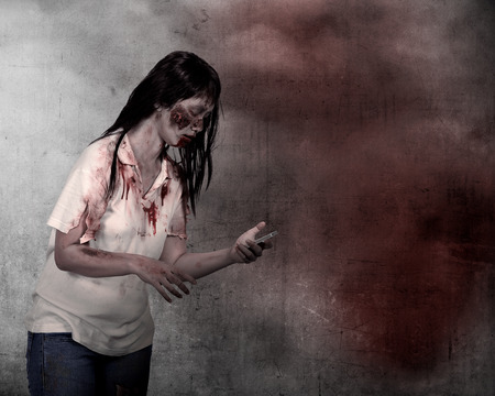 lady on phone: Female zombie holding cellphone over grunge background