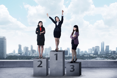 win: Business person standing on the podium. Business reward concept