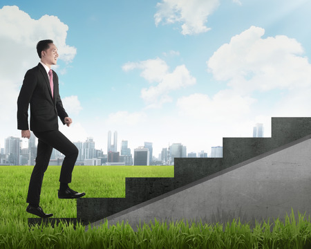 men standing: Confident business person walking upstairs. Business career concept