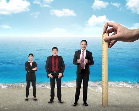 appraisal: Hand holding wooden ruler, mesuring employee performance. Working appraisal concept Stock Photo