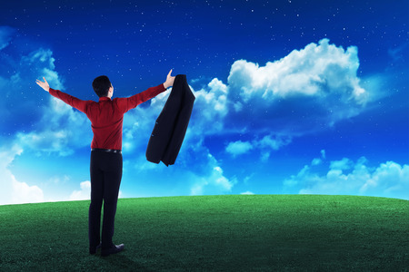 person looking: Business person looking the sky, standing on the grass Stock Photo