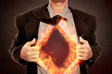 super hero: Business man tears open his shirt in a super hero fashion getting ready to save the day with fire around his shirt