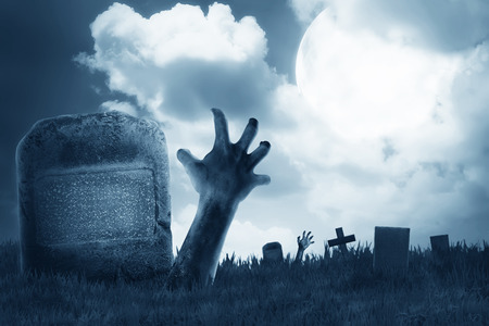 spooky graveyard: Zombie hand out from the graveyard. Halloween concept