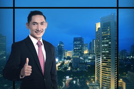 buonanotte: Asian Business man show pollice in su sopra sfondo citt� di notte Archivio Fotografico