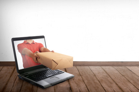 Hand giving a box out of laptop screen. Online shopping concept